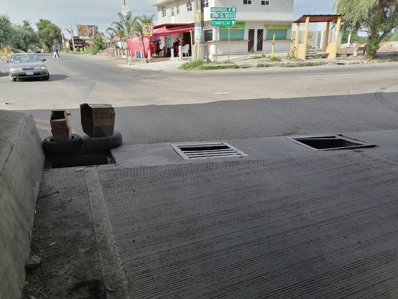 Vecinos exigen reparar coladeras en puente de Xalmimilulco