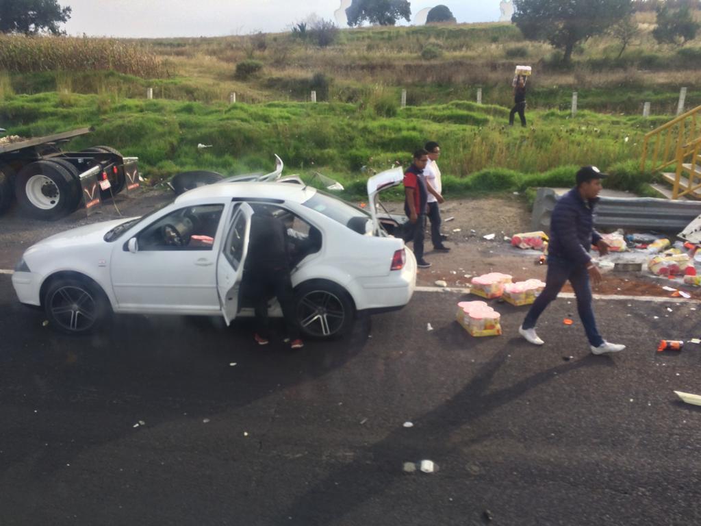 Rapiña de abarrotes tras camión volcado en la México-Puebla