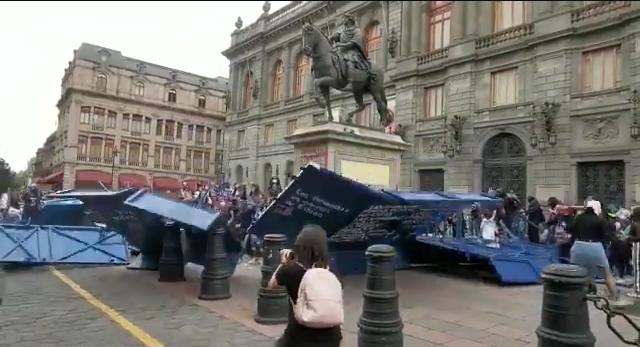 Mujeres en manifestación tiran vallas en Palacio Nacional